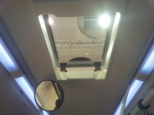 electric escape hatch with single pane glass on a city bus
